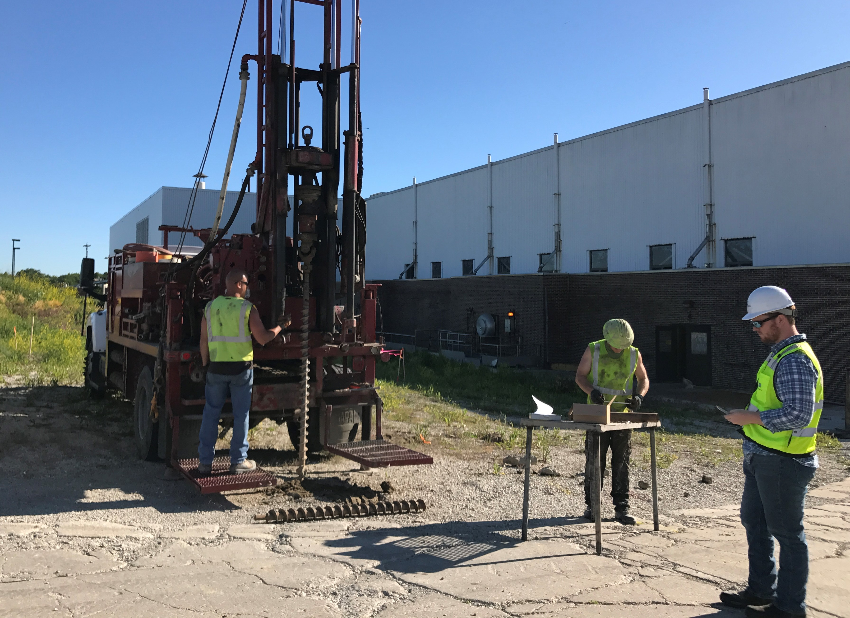 three men with drill rig